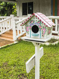 Colorful wooden nesting box. In front of the house Stock Photography