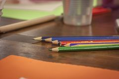 Colorful wooden pencils on the table. Colorful wooden pencils leaning over a drawing board in a classroom of a design school Stock Images