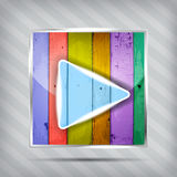 Colorful wooden play icon. On the striped background Royalty Free Stock Image