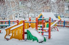Colorful wooden playground under snow. stock photo