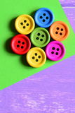 Colorful wooden round buttons laid out in the shape of a flower on a green paper sheet. Wooden background with copy space for text Royalty Free Stock Photos