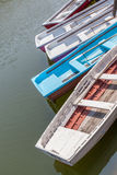 Colorful wooden rowboats anchor at the pier. Royalty Free Stock Image