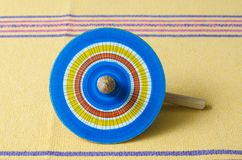 Colorful wooden spinning against yellow tablecloth. Mexican toys