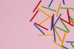 Colorful wooden sticks against pink background royalty free stock images