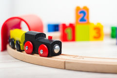 Colorful wooden toy train. And blocks on laminated floor royalty free stock images