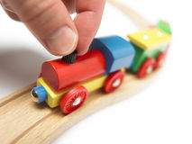 Colorful wooden toy train with hand isolated on white Royalty Free Stock Photo