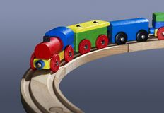 Colorful wooden toy train on tracks. Studio photography of a colorful wooden toy train in dark bluish back Royalty Free Stock Image