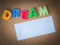 Colorful Wooden word DREAM with piece of White paper on cork board. 1 royalty free stock images