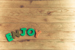 Colorful wooden word Enjoy on wooden floor2 Royalty Free Stock Image