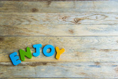Colorful wooden word Enjoy on wooden floor Royalty Free Stock Photos