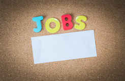 Colorful Wooden word JOBS with piece of White paper on cork board Stock Images
