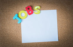 Colorful Wooden word JOBS with White paper on cork board Stock Photography