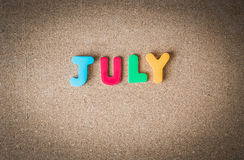 Colorful wooden word JULY on cork board with selective focus Stock Photography