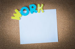 Colorful Wooden word WORK with White paper on cork board Stock Photos