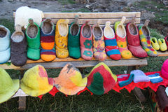 Colorful Woolen Shoes and Hats. Colorful woolen and hats made by Romanian peasants and hung on strings for sale in front of a traditional house in Viscri, a Royalty Free Stock Photography
