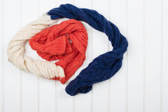 Colorful woolly hat and scarf on white wooden background. Royalty Free Stock Photos