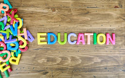 The colorful word `EDUCATION` next to a pile of other letters. Over the old wood board Royalty Free Stock Photography