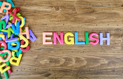 The colorful word `ENGLISH` next to a pile of other letters. Over the old wood board Royalty Free Stock Photos