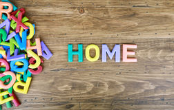 The colorful word `HOME` next to a pile of other letters Royalty Free Stock Images