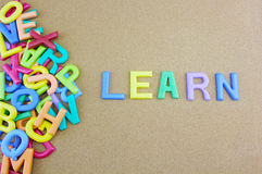The colorful word LEARN next to a pile of other letters. Over the brown board surface composition Stock Image