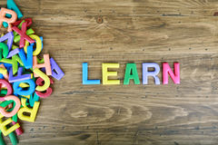 The colorful word `LEARN` next to a pile of other letters. Over the old wood board Stock Photo