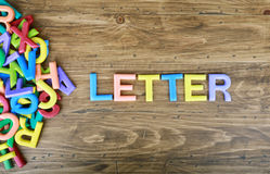 The colorful word `LETTER` next to a pile of other letters. Over the old wood board Stock Photography
