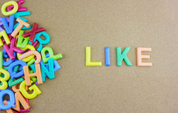 The colorful word LIKE next to a pile of other letters. Over the brown board surface composition Stock Photography