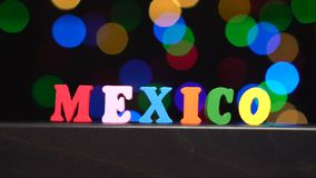 Colorful word `Mexico` from multi-colored wooden letters in front of abstract blurred lights bokeh background stock video