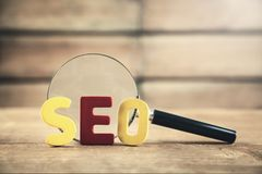 Colorful word Seo with magnifying glass. Search engine optimisat. Ion concept royalty free stock photography