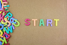 The colorful word START next to a pile of other letters. Over the brown board surface composition Stock Photos