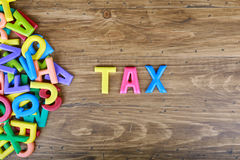 The colorful word `TAX` next to a pile of other letters. Over the old wood board Stock Photo
