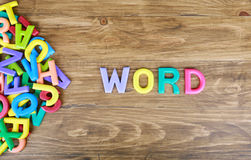 The colorful word `WORDS` letters over the old wood board. The colorful word `WORDS` next to a pile of other letters over the old wood board royalty free stock image