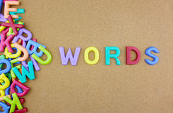 The colorful word WORDS next to a pile of other letters. Over the brown board surface composition Stock Photos