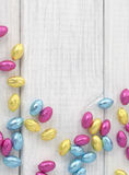 Colorful Wrapped Chocolate Easter Eggs Scattered on White Board Background with room or space for text, copy or words. Vertical Royalty Free Stock Image