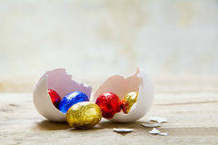 Colorful wrapped chocolate eggs in a white chicken eggshell on a Stock Image