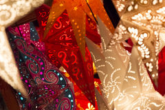 Colorful xmas stars. Shiny red orange golden stars at european christmas market. Part of series Royalty Free Stock Image