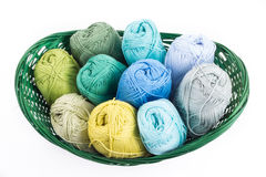Colorful yarn balls in a straw basket. Isolated on white background Stock Photo