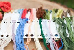 Colorful yarn for crafts. Colored threads for embroidery on a wooden table stock image