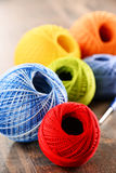 Colorful yarn for crocheting and hook on wooden table Stock Photos