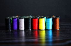 Colorful yarn for sewing on the spool. Colorful yarn for sewing on the spool in a black background Royalty Free Stock Photos