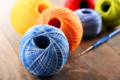 Colorful yarns for crocheting and hook on wooden table Stock Photography