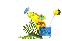Colorful yellow and blue summer cocktails decorated with tropical fruits, umbrellas and straws on white background with palm tree. Leaves. Copy space stock photo