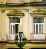 Colorful yellow Cuban building with white shutters. In historic Havana royalty free stock photos