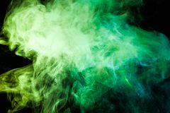 Background from the smoke of vape. Colorful yellow  and green a smoke  on a black isolated background. Background from the smoke of vape Stock Image