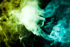 Background from the smoke of vape. Colorful yellow  and green a smoke  on a black isolated background. Background from the smoke of vape Royalty Free Stock Photography