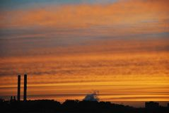 Colorful yellow orange dark dramatic evening sky over industrial royalty free stock image
