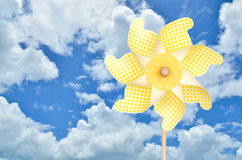 Colorful yellow pinwheel over blue sky with clouds Royalty Free Stock Photos