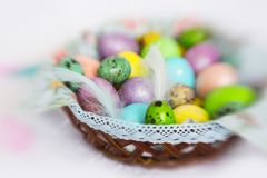 Colorful - yellow, violet, light blue, peach color Easter eggs with feathers in wicker basket. With lace on white tablecloth royalty free stock images
