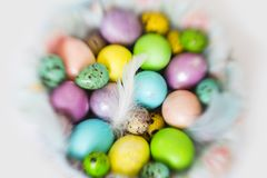 Colorful - yellow, violet, light blue, peach color Easter eggs with feathers in wicker basket. With lace on white tablecloth royalty free stock photo