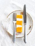 Colorful piece of cake on a porcelain dish with siverware royalty free stock photography
